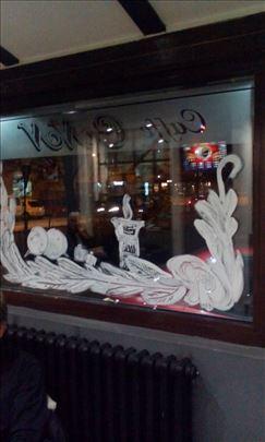Crtanje novogodišnjih ukrasa na prozorima lokala